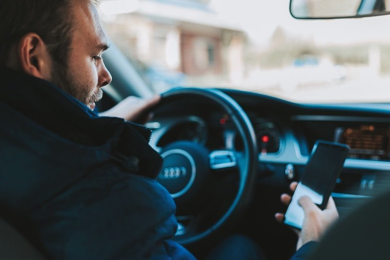 man behind wheel of a car texting